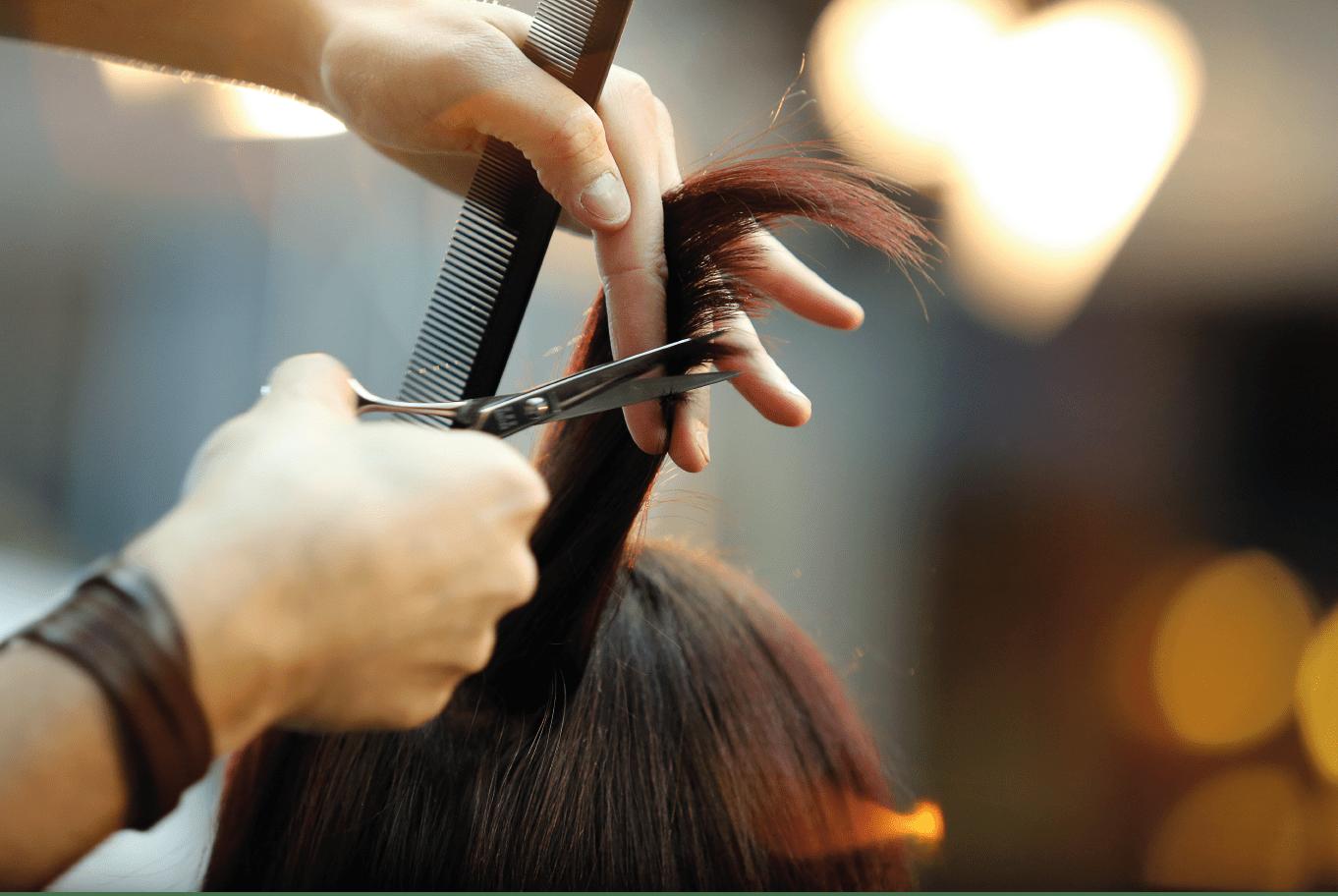 На фото – парикмахер стрижет волосы